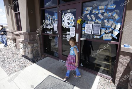 Young girl turns away after finding the front door locked at C&C Coffee and Kitchen, in Castle Rock, Colo. The small restaurant was closed Tuesday after owners defied a public order to not offer dine-in service to customers, which they did on Sunday, in an effort to stop the spread of the new coronavirus