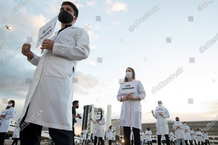 A group of nurses perform a symbolic act on International Nursing Day, in the Esplanada dos Ministerios, in honor of colleagues who have died from COVID- 19, in Brasilia, Brazil, 12 May 2020. Around 100 professionals wore white coats, posters with the names of the victims of the coronavirus, and lit candles. According to the Federal Council of Nursing (Cofen), until this Tuesday, 109 health professionals have lost their lives due to the pandemic.