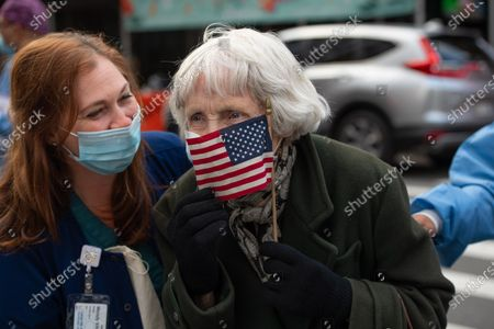 Stock Photo of An old lady wearing a mask and holding a USA flag outside of Lenox Hill Hospital at the 7pm cheer during the COVID-19 pandemic.