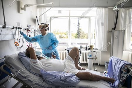 Physical therapist Caroline Baunsoee Nielsen (standing) attends to 54-year-old coronavirus patient Salim Aladdin (lying) at the pulmonary medicine unit of Bispebjerg Hospital in Copenhagen, Denamark, 07 May 2020.
