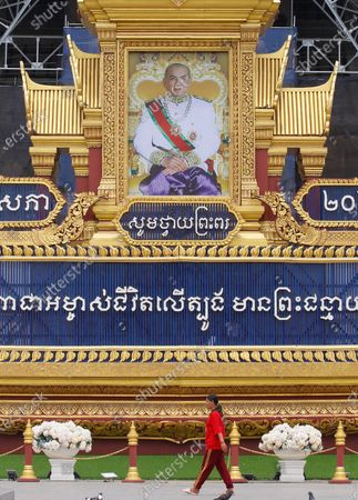 A Cambodian woman walks past a huge portrait of Cambodia's King Norodom Sihamoni on display in front of the Royal Palace in Phnom Penh, Cambodia, 13 May 2020. The monarch's birthday celebrations are held from 13 to 15 May.