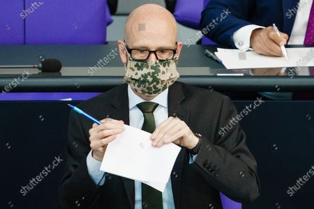 State secretary at the Defense Ministry Peter Tauber wears a face mask with a camouflage pattern during a Aktuelle Stunde current debate session on working conditions in the meat producing industry at the German parliament 'Bundestag' in Berlin, Germany, 13 May 2020. Workers of slaughterhouses in Germany became infected with the coronavirus due to accommodating conditions without options for social distancing. The German Bundestag discusses cheap wages and working conditions in the meat-processing industry.