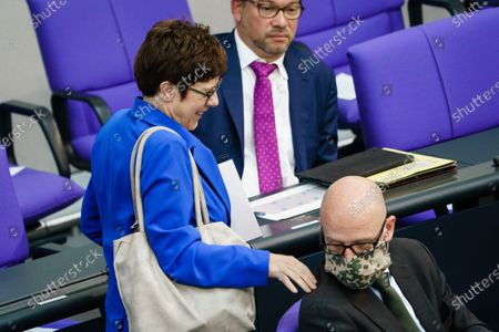 German Defense Minister Annegret Kramp-Karrenbauer (L) says hello to state secretary at the Defense Ministry Peter Tauber who wears a face mask with a camouflage pattern (R) prior to a beginning of a debate on the German Federal Armed Forces (Bundeswehr) deployment on Mali (EUTM) at the German parliament 'Bundestag' in Berlin, Germany, 13 May 2020. The cabinet of the German government already decided an extension of the Mali mission of the Bundeswehr. The German parliament discusses the subject on 13 May 2020.