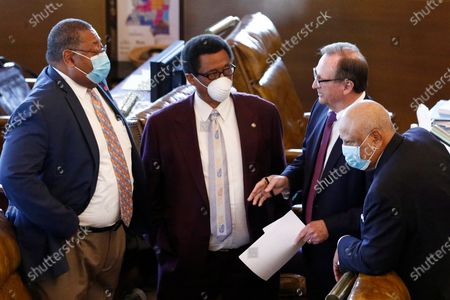 Democratic Sens. Robert Jackson, left, of Marks; Samson Jackson, second from left, of DeKalb; and Joseph Thomas Jr., right, of Yazoo City, confer with Republican President Pro Tem Dean Kirby, of Pearl, as they wait to vote on a coronavirus relief bill for small businesses, at the Capitol in Jackson, Miss
