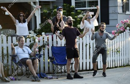 President Gabrielle Carteris, far right, and her husband Charles Isaacs, center, are among the cheering spectators at musician Adam Chester's weekly neighborhood performance in the Sherman Oaks section of Los Angeles. Normally, Chester is a surrogate Elton John, who sings and plays the rock superstar's parts at rehearsals. With that work on hold, Chester has been giving concerts to his neighbors from a safe social distance in front of his house
