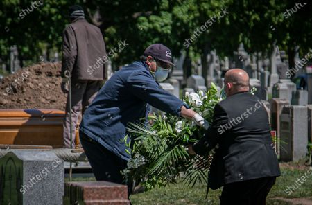Stock Photo of Robert Salerno, right, funeral director with McLaughlin & Sons funeral home in Brooklyn, hands off a wreath to a cemetery worker during a burial, both wearing masks because of coronavirus restrictions, at Holy Cross Cemetery in the Brooklyn borough of New York. To help prevent the spread of the coronavirus, the casket is lowered and covered before relatives are allowed to the gravesite, following guidelines from the National Funeral Directors Association, according to a spokesman for the funeral home