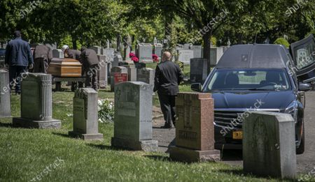 Robert Salerno, right, funeral director with McLaughlin & Sons funeral home in Brooklyn, keeps his distance as cemetery workers prepare to lower a casket with no family present at the gravesite because of coronavirus restrictions, at Holy Cross Cemetery in the Brooklyn borough of New York. To help prevent the spread of the coronavirus, the casket is lowered and covered before relatives are allowed to the gravesite, following guidelines from the National Funeral Directors Association, according to a spokesman for the funeral home