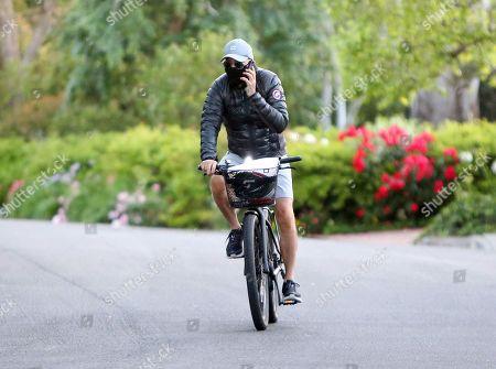 Michael Keaton riding a bike