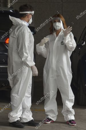 Stock Image of Actress Mariana Seoane and Actor Julio Camejo wear protective suit while delivery medical supplies at Cuajimalpa Hospital to support to health workers during the Coronavirus (COVID-19) pandemic.