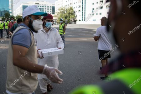 Volunteers distribute meals to people wearing protective masks during the Muslims holy month of Ramadan in Dubai, United Arab Emirates, 14 May 2020. Sheikh Mohammed Bin Rashid Al-Maktoum, the ruler of Dubai, launched an initiative to distribute ten million meals or food parcels to support vulnerable individuals and families affected by the ongoing pandemic of the Covid-19 disease.