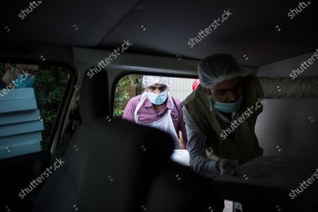 Restaurant workers load meals inside a vehicle for distribution during the Muslims holy month of Ramadan in Dubai, United Arab Emirates, 14 May 2020. Sheikh Mohammed Bin Rashid Al-Maktoum, the ruler of Dubai, launched an initiative to distribute ten million meals or food parcels to support vulnerable individuals and families affected by the ongoing pandemic of the Covid-19 disease.