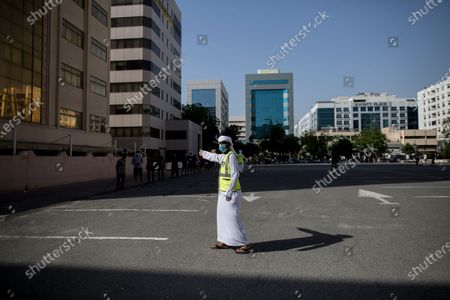 A volunteer organizes queue of people waiting for meals during the Muslims holy month of Ramadan in Dubai, United Arab Emirates, 14 May 2020. Sheikh Mohammed Bin Rashid Al-Maktoum, the ruler of Dubai, launched an initiative to distribute ten million meals or food parcels to support vulnerable individuals and families affected by the ongoing pandemic of the Covid-19 disease.
