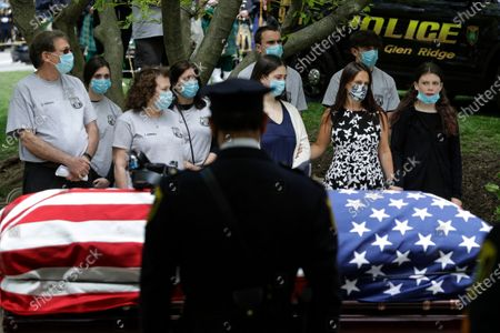 Natalie Roberts, right, and her mother Alice Roberts, second from right, react with loved ones during a memorial service for Glen Ridge Police Officer Charles Roberts, Glen Ridge, N.J. Roberts died of complications related to COVID-19. AP Photo/Frank Franklin II