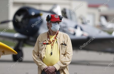 Joe Johnston wears a face mask while waiting to marshall planes on to the runway as dozens of local aviators take flight from Rocky Mountain Metro Airport while the state of Colorado creaks back to life with the easing of restrictions to check the spread of the new coronavirus, in Broomfield, Colo. More than 30 planes took part in the air parade, which stretched from the city of Longmont south to the community of Castle Rock. The money raised by the aviators will be donated to the Help Colorado Now program, a COVID-19 relief fund