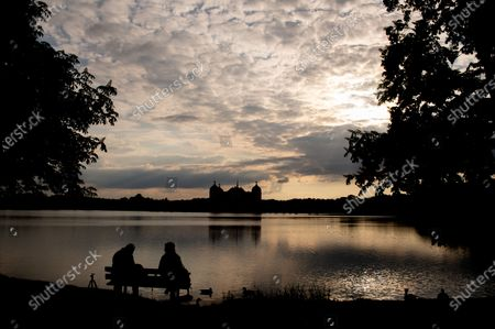 A couple sit on a bench along a lake near Moritzburg Castle, in Moritzburg, Germany, during the sunset hours on 14 May 2020. The famous Saxony castle is named after Duke Moritz, who had it built as a hunting lodge near his residence in Dresden in 1542. Moritzburg Castle hosts apart from many other contemporary treasures one of the most outstanding collections of hunting trophies in Europe.