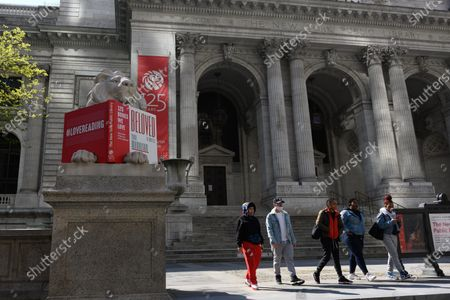Stock Image of People walk past the lion statues in front of the New York Public Library during the coronavirus outbreak. The New York Public Library's historic marble lions turn 109 years oldo n May 11th. Carved by the Piccirilli Brothers in 1911, Patience and Fortitude have long guarded the library's Stephen A. Schwarzman Building on Fifth Avenue.