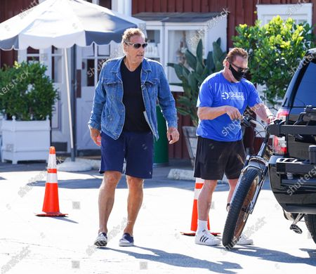 Arnold Schwarzenegger and Ralf Moeller are seen getting ready to ride their bikes during quarantine