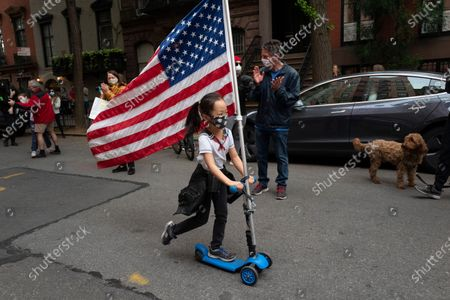"""Ai Feng, 6, parades up and down her block with a United States flag in the Greenwich Village neighborhood, during the coronavirus pandemic in New York. She and her neighbors turned out to honor healthcare workers and to sing along with Liza Minnelli's recording of the """"Theme from New York, New York"""