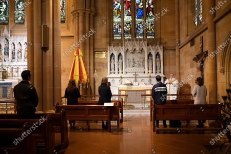Father Don Richardson (2-R) holds a holy mass at St Mary's Cathedral in Sydney, Australia, 15 May 2020. Catholic churches across New South Wales (NSW) have opened their doors for private prayer, confession and small-scale masses amid easing of COVID-19 restrictions.