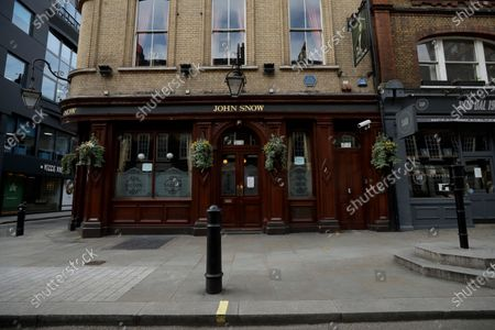The John Snow pub stands temporarily closed during the nationwide coronavirus lockdown, with a replica of the original water pump, at right, that in 1854 Dr John Snow tracked down as the drinking water source of a cholera outbreak that killed more than 500 people, the first time anyone had identified cholera as a water-borne disease, on Broadwick Street, in the Soho area of central London, . Snow is considered one of the founders of modern epidemiology