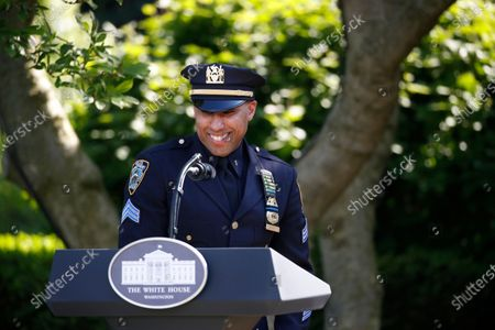 Stock Photo of New York City police officer Spencer Garrett smiles as he speaks during a presidential recognition ceremony in the Rose Garden of the White House, in Washington. Garrett has returned to duty after recovering from coronavirus