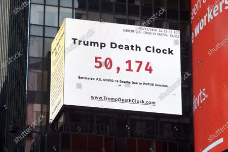 "An electronic sign displays the ""Trump Death Clock"" in Times Square in New York City. Created by by filmmaker Eugene Jarecki, the 56-foot billboard displays the estimated portion of U.S. COVID-19 deaths caused by President Trump's delayed response to the pandemic."