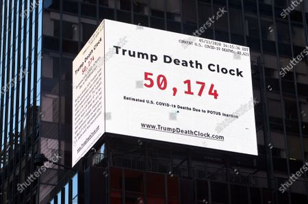 "Stock Photo of An electronic sign displays the ""Trump Death Clock"" in Times Square in New York City. Created by by filmmaker Eugene Jarecki, the 56-foot billboard displays the estimated portion of U.S. COVID-19 deaths caused by President Trump's delayed response to the pandemic."