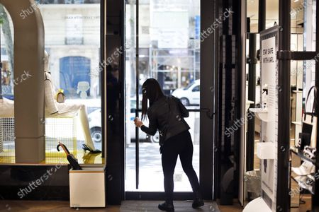 Salesperson cleans the entrance door of a Karl Lagarfeld' shop, in Paris, . Karl Lagerfeld, the eponymous luxury brand of the late German designer, opened its doors this week for the first time to customers since closures around France linked to the coronavirus pandemic