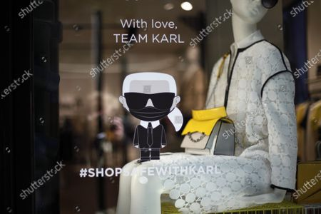 Sticker representing late fashion designer Karl Lagarfeld with a face mask is stuck on the front window of a Karl Lagarfeld' shop, in Paris, . Karl Lagerfeld, the eponymous luxury brand of the late German designer, opened its doors this week for the first time to customers since closures around France linked to the coronavirus pandemic