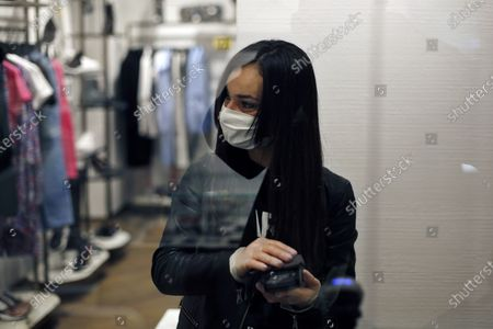 Stock Photo of Salesperson wearing a face mask for protection against the coronavirus waits for customers in a Karl Lagarfeld' shop, in Paris, . Karl Lagerfeld, the eponymous luxury brand of the late German designer, opened its doors this week for the first time to customers since closures around France linked to the coronavirus pandemic