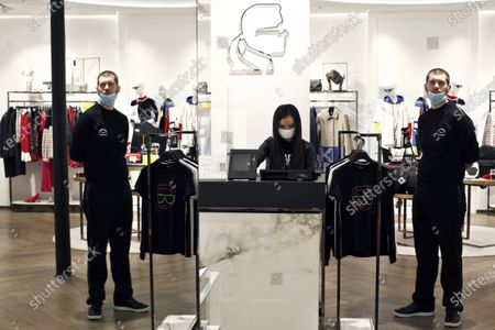 Salespersons wearing a face mask for protection against the coronavirus wait for customers in a Karl Lagarfeld' shop, in Paris, . Karl Lagerfeld, the eponymous luxury brand of the late German designer, opened its doors this week for the first time to customers since closures around France linked to the coronavirus pandemic