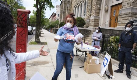 Volunteer Robin Clark (C) hands out packs of free reusable masks outside of the Bethany Baptist Church in Brooklyn, New York, USA, on 15 May 2020. Restrictions requiring the shut down of all non-essential businesses are currently in place around the United States to stop the spread of the highly-contagious coronavirus. These restrictions are having massive economic implications and some local and federal politicians are being to suggest plans for lifting some rules in an effort to get parts of the economy going again; many health officials are worried this will lead to another spike in COVID-19 cases.