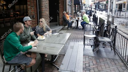 Mike Kapeluck, left to right, Michael Cole, and Ashley Healy have lunch outside of the The Corner Alley during the coronavirus pandemic, in Cleveland. Republican Ohio Gov. Mike DeWine has said that 90% of the state's economy will be back online this weekend with Ohioans having returned to offices, factories, construction jobs and retail stores, and now outdoor eating