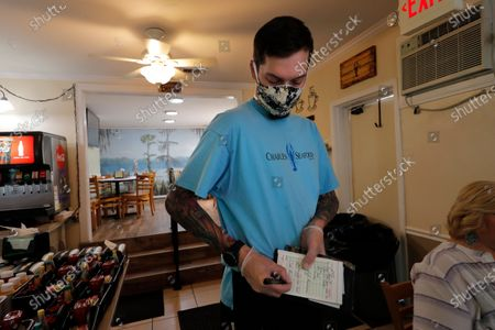 Stock Picture of Waiter Kevin Patterson takes orders from indoor sit-down customers, for the first time since the state shutdown, at Charles Seafood Restaurant Luxurie Nail Spa in Harahan, La., . Once a hot spot for coronavirus infections, Louisiana is officially easing up Friday on economically devastating business closures and public gathering restrictions that Gov. John Bel Edwards credits with slowing the spread of the virus