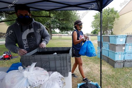 Nicholas Juarez, left, and Jessica Bacon, right, of Be A Champion Inc., hand out bags of food at a distribution site in Dallas, . The organization that is based out of Houston is working in collaboration with Richardson Independent School District and others to provide meals to families with school-aged children around the state of Texas. Bacon said that since April, Be A Champion has provided over 300,000 meals to families in need