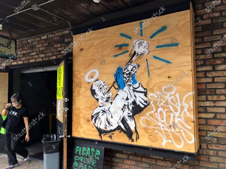 Stock Photo of Woman walks out of a restaurant on Frenchman Street in New Orleans, next to a boarded up window that has been decorated with a painting of musician Louis Armstrong. The clubs and restaurants that are usually packed with people listening to music are closed as the city has fought to slow the spread of the coronavirus
