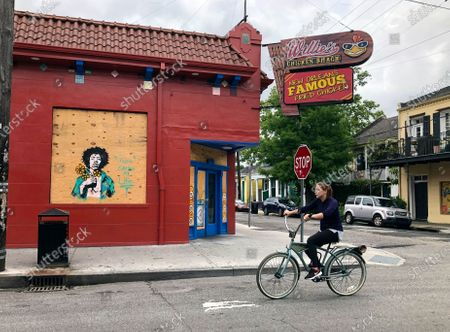 Woman rides by a boarded up window of a business on Frenchman Street, in New Orleans, that has been decorated with a painting of Jimi Hendrix. The clubs and restaurants that are usually packed with people listening to music are closed as the city has fought to slow the spread of the coronavirus