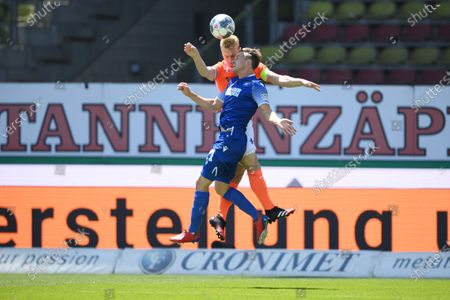 Marco Thiede (front) of Karlsruhe jumps for a header with Fabian Holland of SV Darmstadt 98 during the German Bundesliga second division soccer match between Karlsruher SC and SV Darmstadt 98 at Wildparkstadion in Karlsruhe, Germany, 16 May 2020. The Bundesliga and Second Bundesliga is the first professional league to resume the season after the nationwide lockdown due to the ongoing Coronavirus (COVID-19) pandemic. All matches until the end of the season will be played behind closed doors.