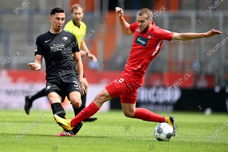 Robert Zulj (L) of Bochum challenges Patrick Mainka of Heidenheim during the German Bundesliga Second Division soccer match between VfL Bochum 1848 and 1. FC Heidenheim 1846 at Vonovia Ruhrstadion in Bochum, Germany, 16 May 2020. The Bundesliga and Second Bundesliga are the first professional leagues to resume the season after the nationwide lockdown due to the ongoing Coronavirus (COVID-19) pandemic. All matches until the end of the season will be played behind closed doors.