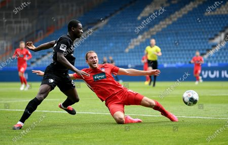 Jordi Orsei Tutu (L) of Bochum challenges Jonas Foehrenbach of Heidenheim during the German Bundesliga Second Division soccer match between VfL Bochum 1848 and 1. FC Heidenheim 1846 at Vonovia Ruhrstadion in Bochum, Germany, 16 May 2020. The Bundesliga and Second Bundesliga are the first professional leagues to resume the season after the nationwide lockdown due to the ongoing Coronavirus (COVID-19) pandemic. All matches until the end of the season will be played behind closed doors.