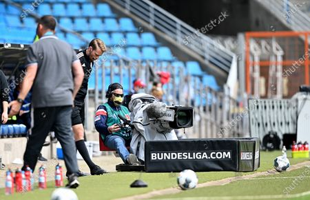 A TV camera man is seen during the German Bundesliga Second Division soccer match between VfL Bochum 1848 and 1. FC Heidenheim 1846 at Vonovia Ruhrstadion in Bochum, Germany, 16 May 2020. The Bundesliga and Second Bundesliga are the first professional leagues to resume the season after the nationwide lockdown due to the ongoing Coronavirus (COVID-19) pandemic. All matches until the end of the season will be played behind closed doors.
