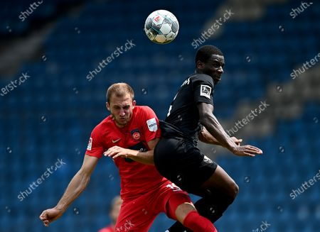 Jordi Osei Tutu (R) of Bochum challenges Jonas Foehrenbach of Heidenheim during the German Bundesliga Second Division soccer match between VfL Bochum 1848 and 1. FC Heidenheim 1846 at Vonovia Ruhrstadion in Bochum, Germany, 16 May 2020. The Bundesliga and Second Bundesliga are the first professional leagues to resume the season after the nationwide lockdown due to the ongoing Coronavirus (COVID-19) pandemic. All matches until the end of the season will be played behind closed doors.