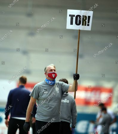 Stock Photo of A member of the Holstein Kiel staff holds up a goal or Tor banner after Holstein Kiel score the second goal during the German Bundesliga Second Division soccer match between SSV Jahn Regensburg and Holstein Kiel at Continental Arena in Regensburg, Germany, 16 May 2020. The Bundesliga and Second Bundesliga are the first professional leagues to resume the season after the nationwide lockdown due to the ongoing Coronavirus (COVID-19) pandemic. All matches until the end of the season will be played behind closed doors.