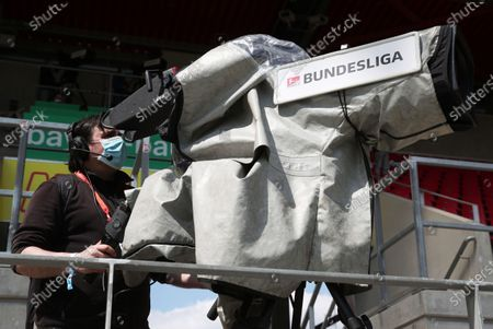 A camera operator wears a face mask inside the stadium before the Second Bundesliga match between SSV Jahn Regensburg and Holstein Kiel at Continental Arena in Regensburg, Germany, 16 May 2020. The Bundesliga and Second Bundesliga are the first professional leagues to resume the season after the nationwide lockdown due to the ongoing Coronavirus (COVID-19) pandemic. All matches until the end of the season will be played behind closed doors.