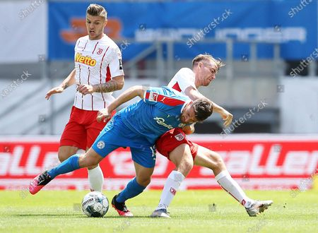 Salih Oezcan (L) of Holstein Kiel is challenged by Max Besuschkow of Jahn Regensburg during the German Bundesliga Second Division soccer match between SSV Jahn Regensburg and Holstein Kiel at Continental Arena in Regensburg, Germany, 16 May 2020. The Bundesliga and Second Bundesliga are the first professional leagues to resume the season after the nationwide lockdown due to the ongoing Coronavirus (COVID-19) pandemic. All matches until the end of the season will be played behind closed doors.