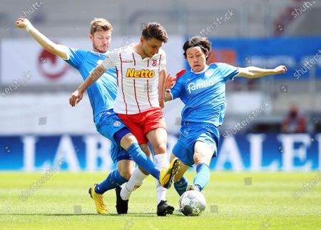 Alexander Muehling (L) of Holstein Kiel and Lee Jae-Sung (R) of Holstein Kiel challenge Charalampos Makridis of Jahn Regensburg during the German Bundesliga Second Division soccer match between SSV Jahn Regensburg and Holstein Kiel at Continental Arena in Regensburg, Germany, 16 May 2020. The Bundesliga and Second Bundesliga are the first professional leagues to resume the season after the nationwide lockdown due to the ongoing Coronavirus (COVID-19) pandemic. All matches until the end of the season will be played behind closed doors.