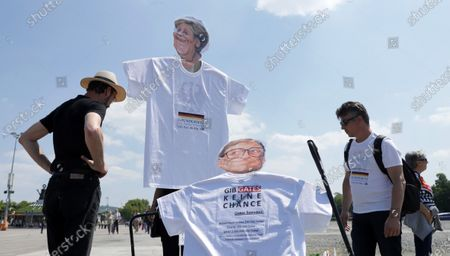 People with banners faces depicting German Chancellor Angela Merkel with the word 'constitution' and US businessman Bill Gates with the phrase 'don't give Gates a chance' during a demonstration of the initiative 'Lateral thinking' in Stuttgart, Germany, 16 May 2020. The demonstration is directed against the Coronavirus restrictions and for basic rights such as freedom of assembly and freedom of religion.
