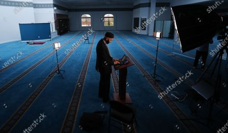 Stock Photo of Imam Omar Suleiman prepares for an online broadcast from an empty mosque in Irving, Texas, . Many places of worship are seeing more people attending online than showed up in person