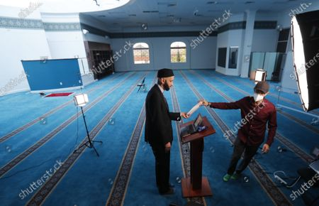 Head of video production, Fawzi Yahya, right, helps Imam Omar Suleiman prepare for an online broadcast from the empty Valley Ranch Islamic Center mosque in Irving, Texas, . Many places of worship are seeing more people attending online than showed up in person
