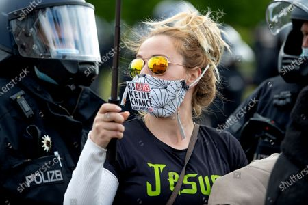 "The Reichstag building, home of the German federal parliament, is mirrored in the glasses of a woman wearing a face mask with the slogan""Don't Give (Bill) Gates A Chance"" during a demonstration against restrictions and measures to prevent the spread of the new coronavirus in Berlin, Germany"